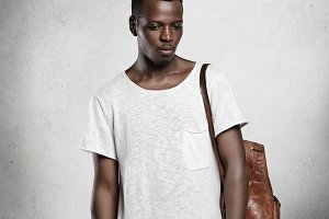 People and lifestyle. Portrait of young attractive African student wearing leather rucksack and white stylish top with copy space for your content, looking down with serious expression on his face