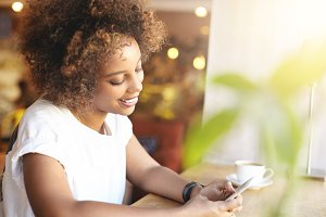 Fashionable African student girl with stylish curly hair using high-speed Internet connection, checking news feed, liking posts with happy smile, having cappuccino, relaxing at cafe after college