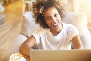 Stylish dark-skinned woman food blogger with curly haircut publishing new posts on social networks, using laptop computer while sitting on sofa at cafeteria on sunny day and having cappuccino
