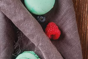 Traditional French sweets. Assorted colorful macaroons with mint green, white and red raspberries, blueberries. Dark wood background. Top view