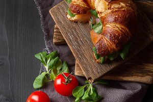 French food for breakfast. Baked Croissant sandwich with salmon and fresh salad leaves sun dried tomatoes on a dark wooden board. Dark wood background. Top view