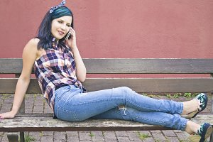 young woman sitting on wooden bench talking to the mobile phone