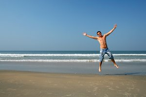 man jumping on the sea beach