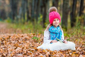 Adorable little girl outdoors at beautiful warm day in autumn forest