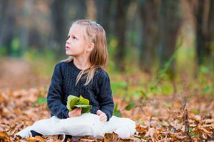 Adorable little girl with colorful leaf at beautiful autumn day