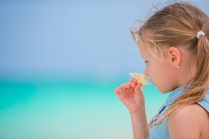 Portrait of adorable little girl with flower frangipani on beach summer vacation