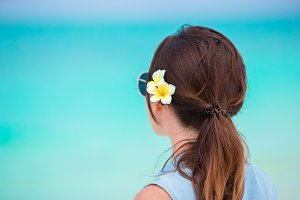 Young beautiful woman during tropical beach vacation. Enjoy suumer vacation alone on the beach with frangipani flowers in her hair