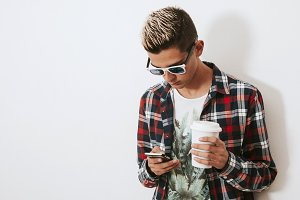 isolated young man with mobile phone and cup of coffee
