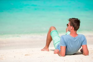 Happy young man enjoying time on white sandy beach
