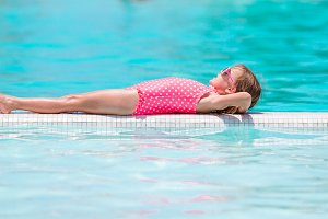 Little happy adorable girl on the edge of infinity swimming pool outdoor