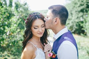 groom kisses beautiful bride