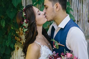 groom and bride kiss outdoors