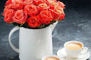 Two cups of espresso and a bouquet of roses