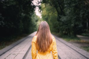 Woman standing backwards on empty tram rails in moody green forest nature. Vintage style photo