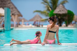 Young mother and little daughter have fun on the edge of swimming pool
