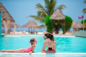 Young mother and little kid on the edge of swimming pool