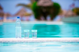Glasses of waters and bottle on the edge of infinity pool