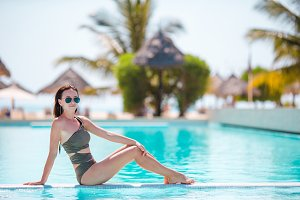 Beautiful young woman relaxing in infiniti pool at luxury hotel