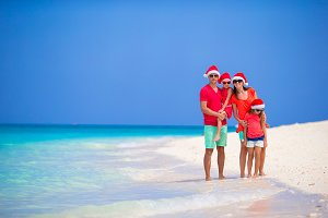 Happy family in Santa Hats during tropical Christmas vacation