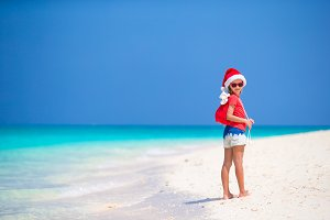 Adorable little girl in Santa hat and a bag with gifts during Christmas beach vacation