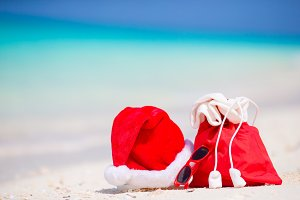 Closeup of red Santa bag and Santa Claus hat on beach. Xmas travel vacation and travel cuprise concept. Beach accessories with Santa Hat on white tropical beach