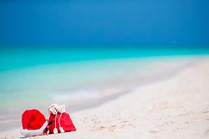 Christmas accessories on white beach. Xmas travel vacation and travel cuprise concept. Beach accessories with Santa Hat on white tropical beach