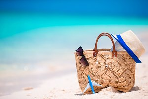 Beach accessories - straw bag, headphones, toy plane and sunglasses on the beach