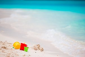 Kids beach toys on white sandy beach background turquiose water