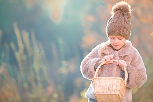 Little girl in autumn park outdoors