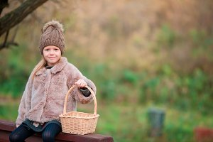 Adorable little girl with a basket in autumn park outdoors