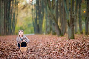 Adorable little girl with a basket in autumn day outdoors in beautiful forest