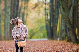 Adorable little girl with a basket in autumn day outdoors