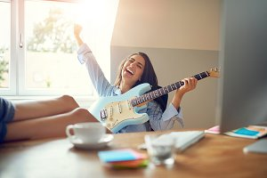 Laughing young woman with guitar and feet on table