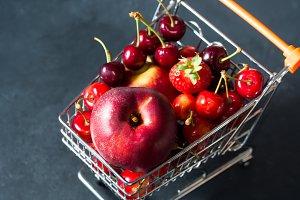 Healthy fruit in supermarket cart on black