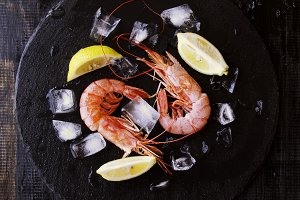 Two raw prawns with lemon and ice cubes, selective focus