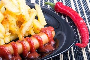 Fried potatoes and sausage close up