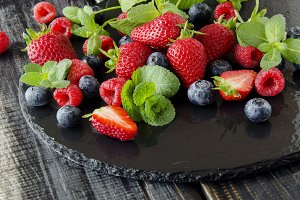 fresh strawberries, raspberries and blueberries on a black background
