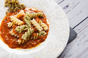 Pasta with tomato sauce decorated with dried flowers