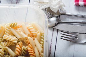 Close up of macaroni in a plastic container with spoons, fork and knife and napkin red and white on a wooden table.