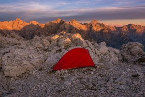 Tent in mountains at sunset