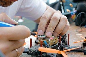 Man's hands welding details assembling FPV drone