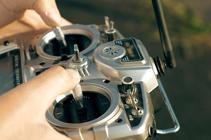 Hands holding a transmitter controlling FPV drone
