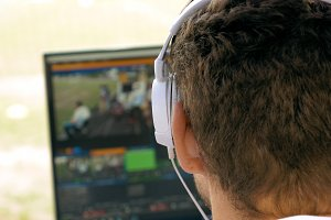 Video broadcast editor with headphones at screen