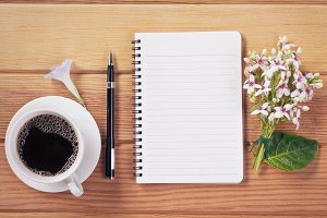 Notebook with coffee cup on table.