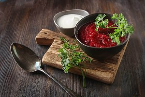 Traditional beetroot soup in a brown plate with Temyan, sour cream. Dark wood background. free space text.
