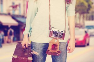 young woman with retro suitcase and camera on city background