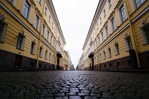 Beautiful St. Petersburg street with paving stone road and old yellow buildings at rainy autumn day, Russia