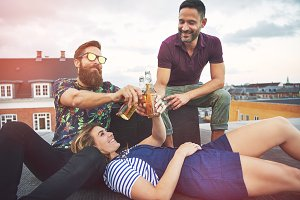 Three adults enjoying beer together on roof