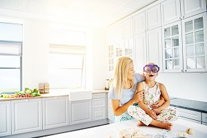 Adorable mother and daughter playing in kitchen