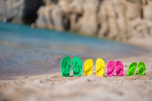 Family flip flops on beach in front of the sea